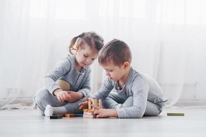 i bambini giocano con un designer di giocattoli sul pavimento della stanza dei bambini. due bambini che giocano con blocchi colorati. giochi educativi per la scuola materna foto