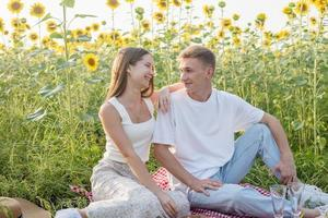 giovane coppia che fa picnic sul campo di girasoli foto