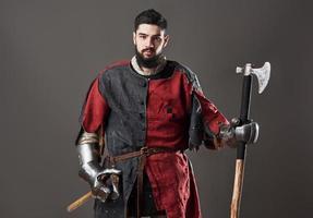 cavaliere medievale su sfondo grigio. ritratto di brutale guerriero faccia sporca con armatura di cotta di maglia vestiti rossi e neri e ascia da battaglia foto