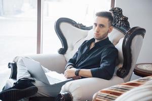giovane uomo d'affari che lavora in un moderno ufficio loft. uomo che indossa una camicia bianca e usa un laptop contemporaneo. sfondo di finestre panoramiche foto