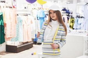 vendita, moda, consumismo e concetto di persone - giovane donna felice con borse della spesa che sceglie vestiti nel centro commerciale o nel negozio di abbigliamento foto