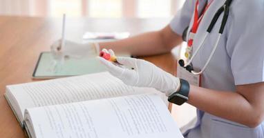 il medico sta cercando informazioni sul trattamento per confrontare i risultati di una provetta per analisi del sangue con un tablet. foto