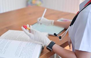 l'infermiera sta registrando i dati del paziente e confrontando i risultati delle provette per analisi del sangue con il tablet. foto