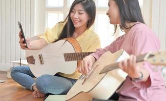 ragazze adolescenti e amici che suonano la chitarra e utilizzano una videochiamata su smartphone. foto