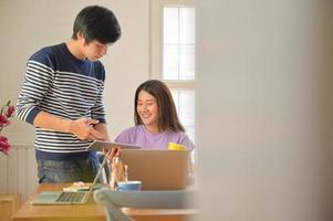 studenti maschi e femmine stanno consultando progetti per le presentazioni degli insegnanti con tablet e laptop. foto