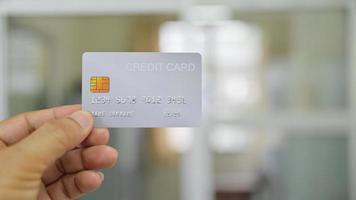primo piano della mano che mostra la carta di credito. foto