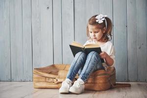 pronto per il grande viaggio. bambina felice che legge un libro interessante che trasporta una grande valigetta e sorride. concetto di viaggio, libertà e immaginazione foto