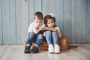 pronto per il grande viaggio. felice bambina e ragazzo che leggono un libro interessante che trasporta una grande valigetta e sorridono. concetto di viaggio, libertà e immaginazione foto