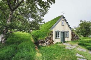 una piccola chiesa in legno e cimitero hofskirkja hof, skaftafell islanda. tramonto panoramico attraverso le chiome degli alberi foto