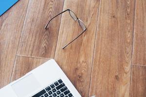 computer portatile occhiali tablet sul pavimento parquet in legno sfondo ampio foto