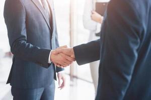 uomini d'affari si stringono la mano, finendo un incontro foto
