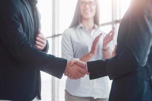 due uomini d'affari fiduciosi che si stringono la mano durante una riunione in ufficio, successo, trattative, saluti e concetto di partner foto