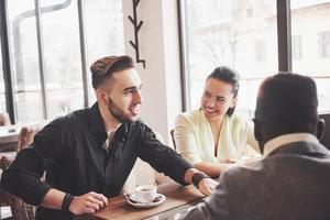concetto di riunione di brainstorming di lavoro di squadra di diversità di avvio. colleghi del team aziendale che condividono il documento di relazione sull'economia mondiale laptop.persone che lavorano pianificazione start up.gruppo giovani hipsters discutendo cafe foto
