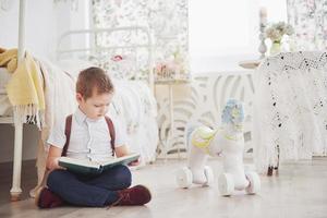 il ragazzino carino sta andando a scuola per la prima volta. bambino con borsa di scuola e libro. il bambino fa una valigetta, la stanza dei bambini su uno sfondo. di nuovo a scuola foto