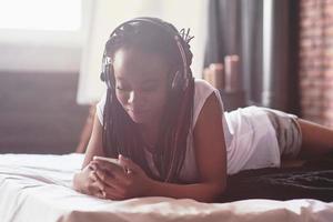 ritratto di bella donna che si sveglia nel suo letto e guarda nel telefono. controllare i social network, inviare sms. la ragazza indossa una maglietta foto