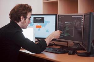 il giovane pericoloso hacker abbatte i servizi governativi scaricando dati sensibili e attivando virus. un uomo usa un computer portatile con molti monitor foto