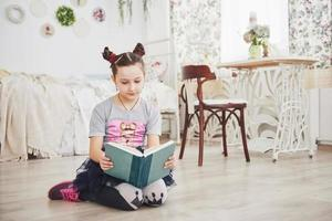 carina bambina che legge un libro in camera da letto. bambino con la corona seduto sul letto vicino alla finestra foto