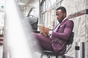 un bellissimo uomo d'affari afroamericano legge un menu in un bar foto