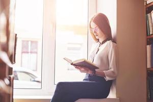 una studentessa si siede sul davanzale di una finestra in una biblioteca e legge un libro foto