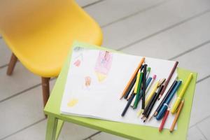 una cornice con un bambino che disegna e matite colorate foto