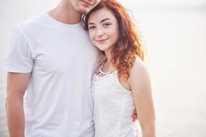 giovane coppia felice che si gode una spiaggia solitaria a cavallo foto