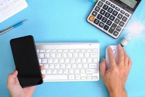 computer funzionante a mano sul tavolo, vista dall'alto sullo spazio di lavoro con apparecchiature per ufficio foto