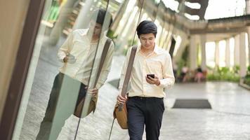 nuova giovane generazione di imprese con una borsa a tracolla guarda lo smartphone in mano per controllare il lavoro. foto