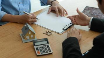 gli agenti di assicurazione stanno introducendo i clienti a firmare contratti di assicurazione immobiliare. foto