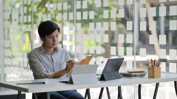 foto ritagliata di uno studente maschio asiatico con un laptop e un fermo che si prepara a completare la sua tesi per finire l'università.