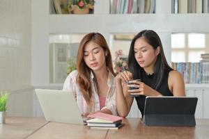 due giovani studentesse con caffè stanno usando un laptop per studiare online a casa nel semestre estivo. foto