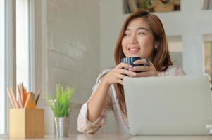 un ritratto di una donna asiatica sorride felicemente con una tazza di caffè durante una pausa dal lavoro in un comodo ufficio. foto
