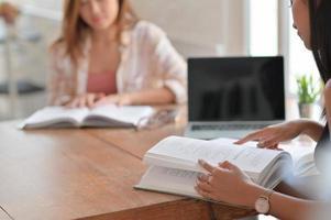 due studentesse asiatiche stanno leggendo duramente per prepararsi agli studi universitari. foto