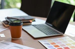 inquadratura ritagliata di una scrivania di un designer di applicazioni con uno schizzo di uno schermo mobile e caffè da asporto nell'ufficio di casa. foto
