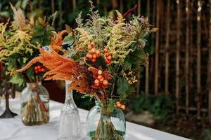 mazzi di fiori in stile rustico sul tavolo in vasi e barattoli di vetro foto