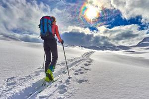 ragazza fa lo sci alpinismo da sola verso il passo di montagna foto