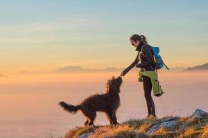 cibo al cane di una ragazza durante un'escursione in montagna foto