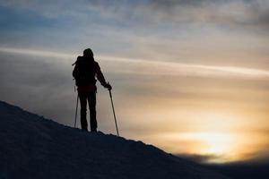 uno sciatore alpinista guarda il tramonto foto