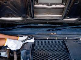 meccanico che tiene in mano una chiave inglese durante la riparazione di un'auto. foto