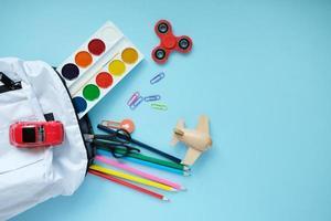 zaino con diversi cancelleria colorata sul tavolo foto