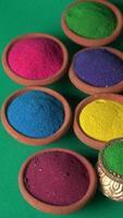 festival di diwali che mostra rangoli colorati in ciotole, lampada di argilla o diya sullo sfondo foto