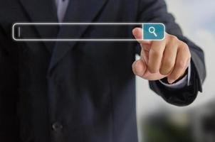 l'uomo d'affari sta toccando una ricerca su uno schermo virtuale. Alla ricerca del concetto di rete di informazioni con spazio di copia. touch screen del computer della pagina di ricerca su Internet. foto