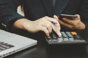 uomo d'affari che tiene una penna e un telefono per premere una calcolatrice. attività finanziarie, bancarie o fiscali e di investimento. foto