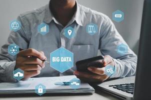 uomo d'affari che tiene la penna e l'icona dello smartphone grande schermo virtuale di dati. concetto di tecnologia aziendale, marketing aziendale, investimenti e analisi dei dati. foto