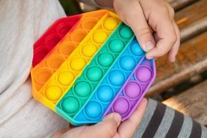 gioco educativo per bambini semplice fossetta, giocattolo sensoriale pop in mano foto