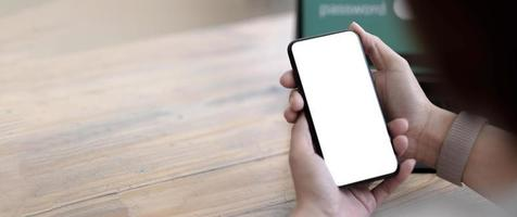 mockup immagine schermo bianco vuoto cellulare phone.women mano che tiene sms utilizzando il cellulare sulla scrivania in ufficio a casa. foto