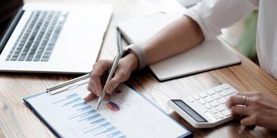 primo piano una donna d'affari lavora su un report grafico finanziario, calcola i costi ei profitti aziendali e si siede alla sua scrivania. foto