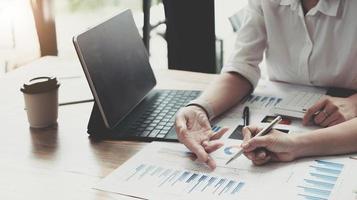 analisi di discussione di due contabili che condividono insieme i calcoli sul budget aziendale e sulla pianificazione finanziaria sulla scrivania in ufficio foto