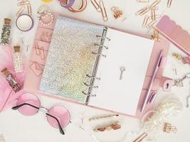 diario aperto con pagina bianca e olografica. agenda rosa con cancelleria carina. vista dall'alto del pianificatore rosa con elementi decorativi. foto di decorazione pianificatore glamour rosa