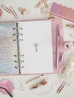 chiave d'argento sulla pagina bianca dell'agenda. diario aperto con pagina bianca e olografica. agenda rosa con cancelleria carina. vista dall'alto del pianificatore rosa con elementi decorativi. foto