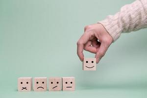 la mano del cliente sceglie una faccia felice. servizio, sondaggio, concetto di comunicazione tariffaria foto